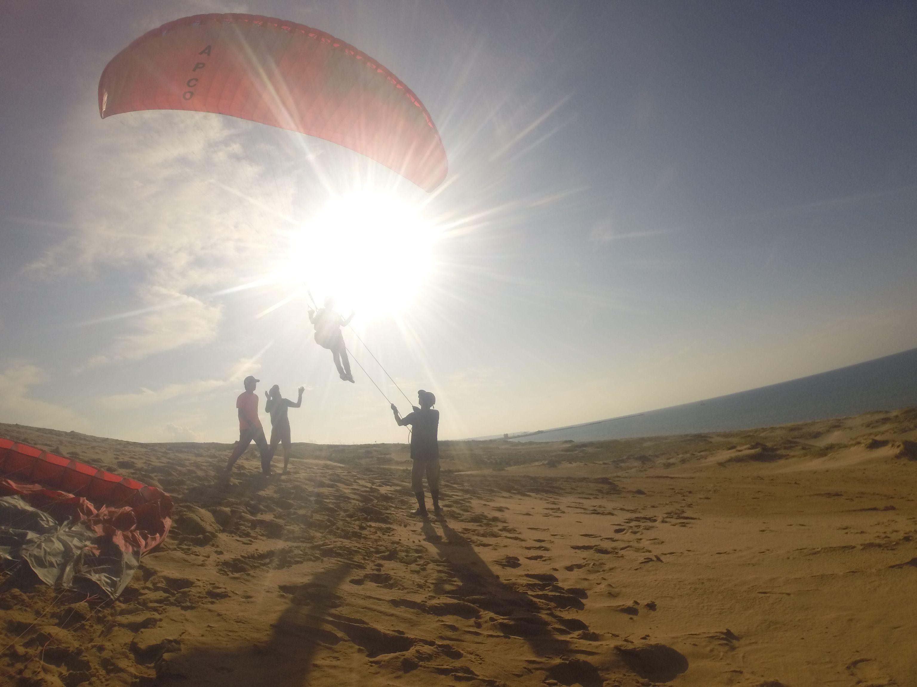 美しい夕陽をバックに飛ぶパラグライダー