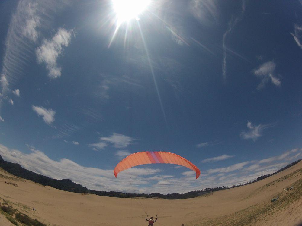 輝く空の鳥取砂丘でパラグライダー体験