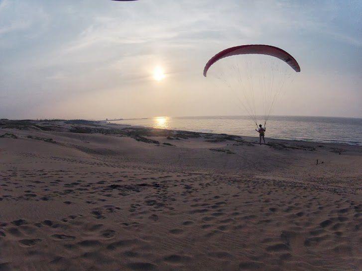 夕日で輝く日本海をバックに砂丘パラグライダー