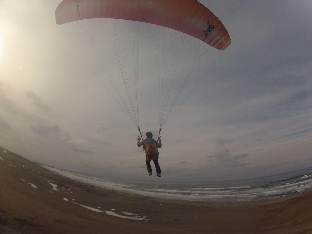 冬の鳥取砂丘を飛ぶパラグライダー