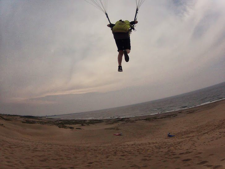 海に向かって豪快に飛ぶ砂丘パラグライダー