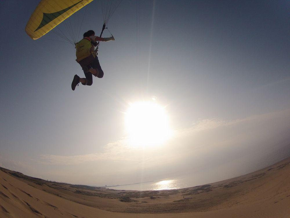 鳥取砂丘から夕日に向かって豪快に飛ぶパラグライダー