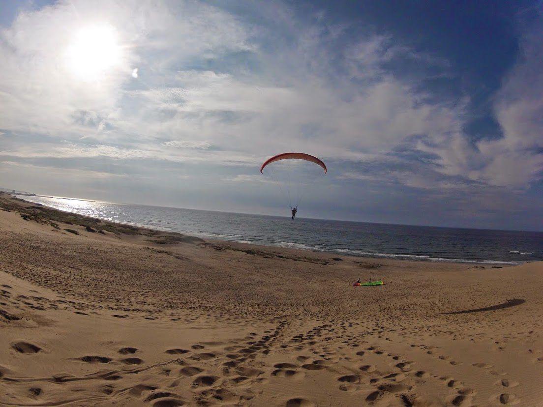 うまく風に乗って浮かぶ砂丘パラグライダー