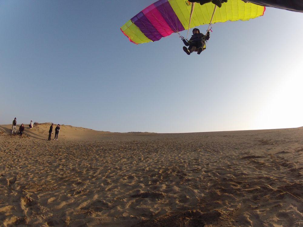 夕日を受けながら鳥取砂丘のパラグライダー