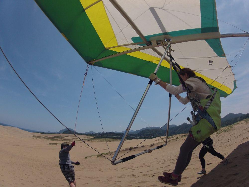 大きく広がる鳥取砂丘を眺めながらハンググライダーで飛ぶ