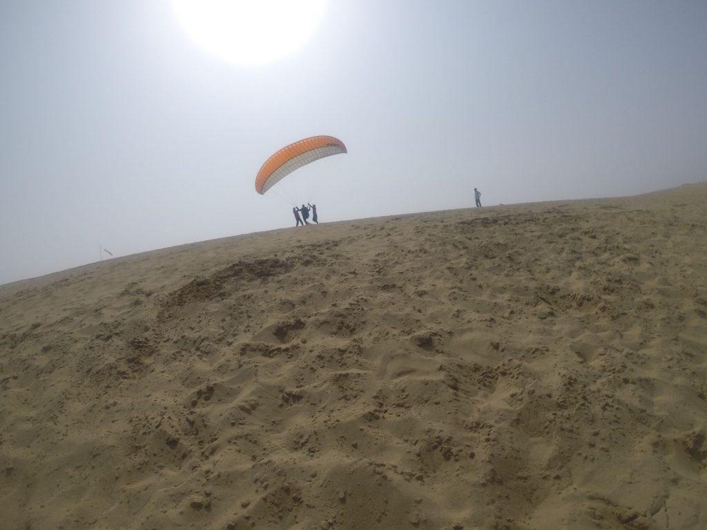 颯爽と丘の上から飛び出すパラグライダー