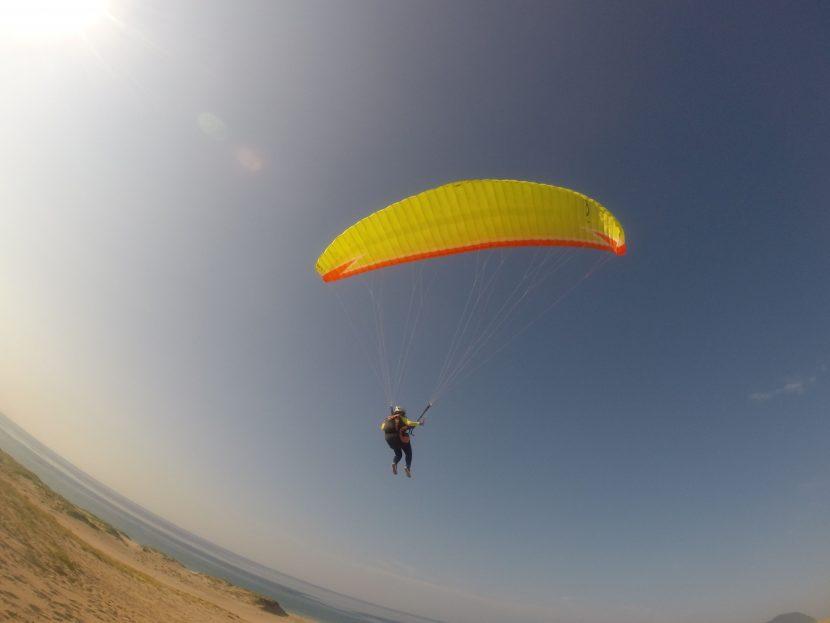 ゆるやかに砂丘上空を舞うパラグライダー