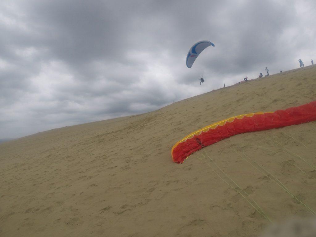 高いところから低いところへ、ゆっくり下降していくパラグライダー