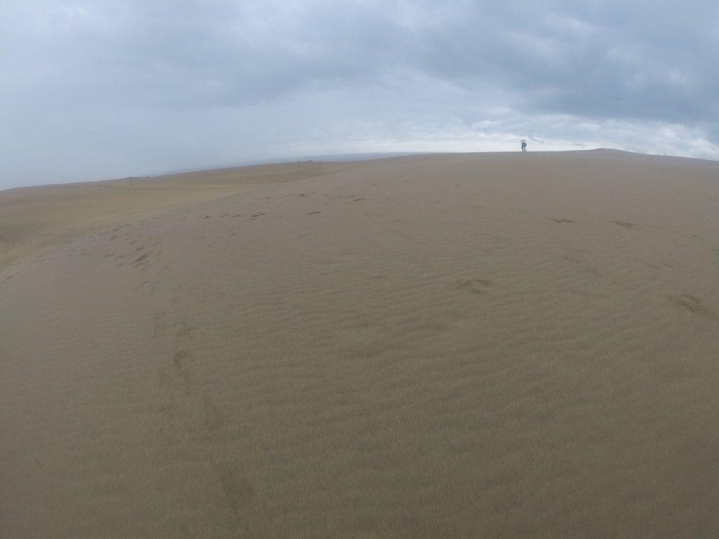 垂れ込める雲が遠くからやってきている朝の鳥取砂丘