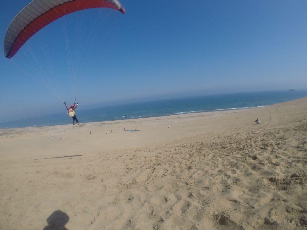 砂の上をぐんぐん滑空するパラグライダー